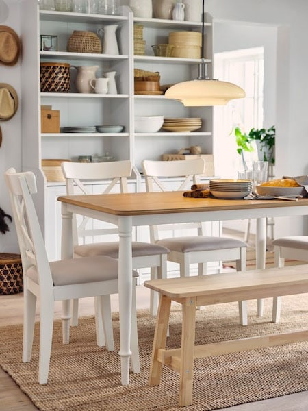 Traditional kitchen with a light dining table, a mixture of traditional wooden dining chairs and a light wooden bench