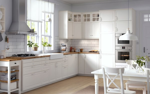 Traditional kitchen with IKEA white kitchen cabinets, wood worktops, glass doors and integrated appliances.