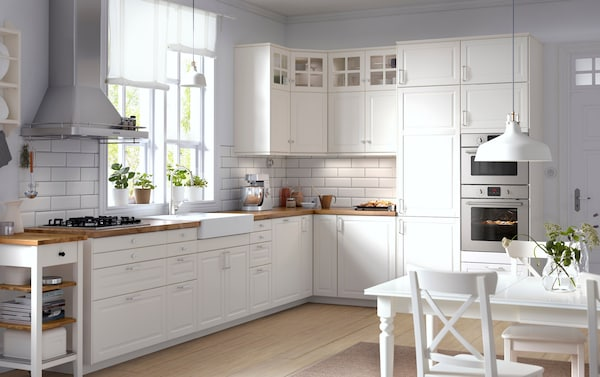 Traditional kitchen with white kitchen cabinets, wooden worktops, glass kitchen doors and integrated kitchen appliances