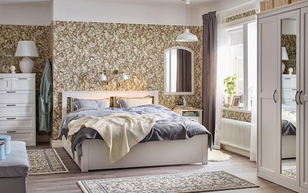 Traditionele slaapkamer met bloemenbehang en een wit SONGESAND bed, nachtkastje en ladekast.