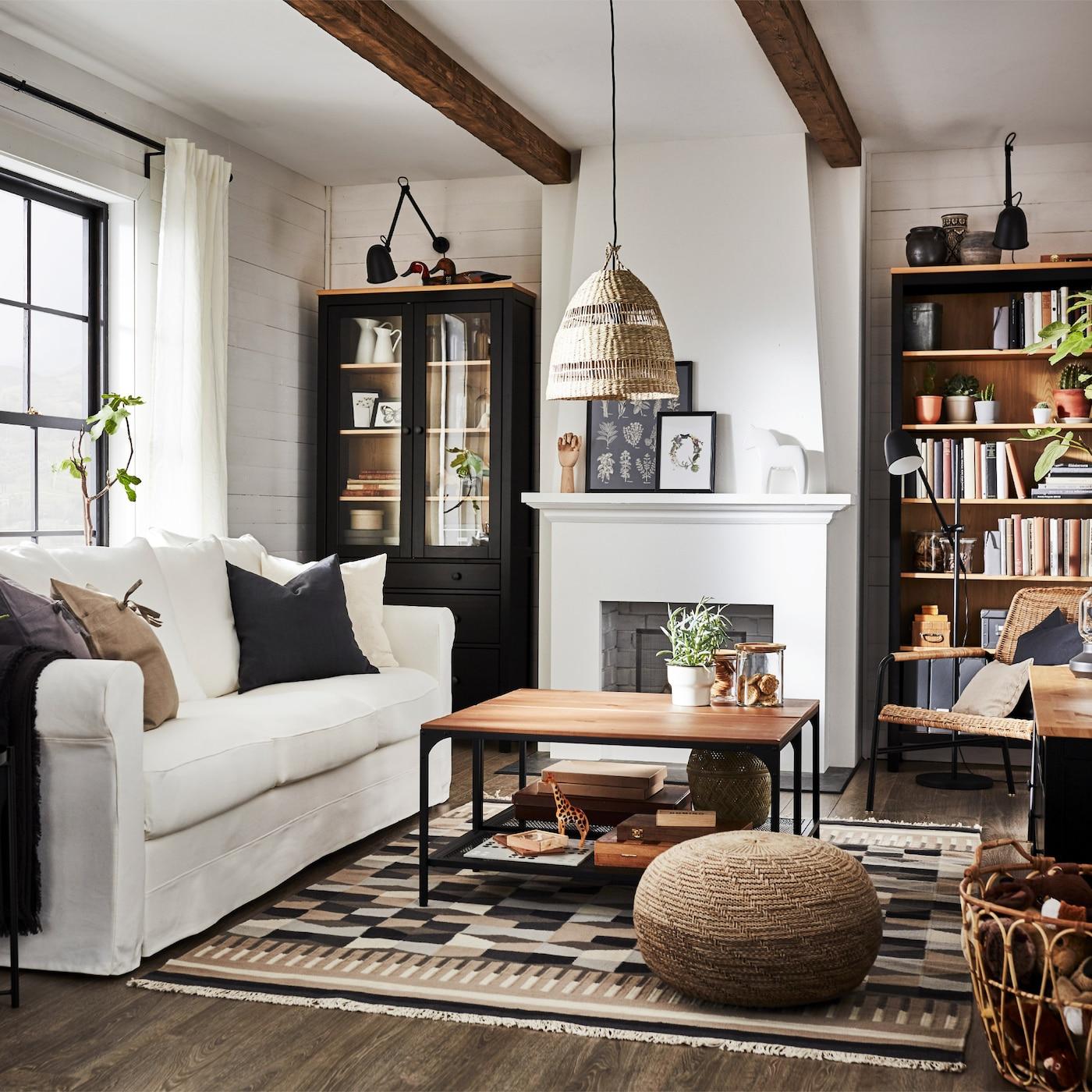 Traditionellt vardagsrum med bokhylla och tv-bänk i svartbrunt/massiv furu, vit soffa och ett vitrinskåp.