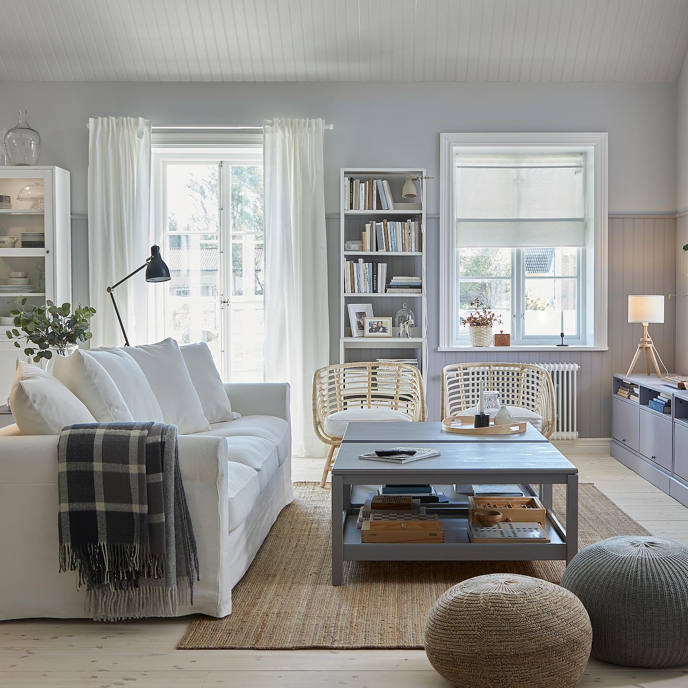 Traditionellt vardagsrum med vit soffa, jutematta, två grå soffbord, grå tv-bänk och två rottingfåtöljer.