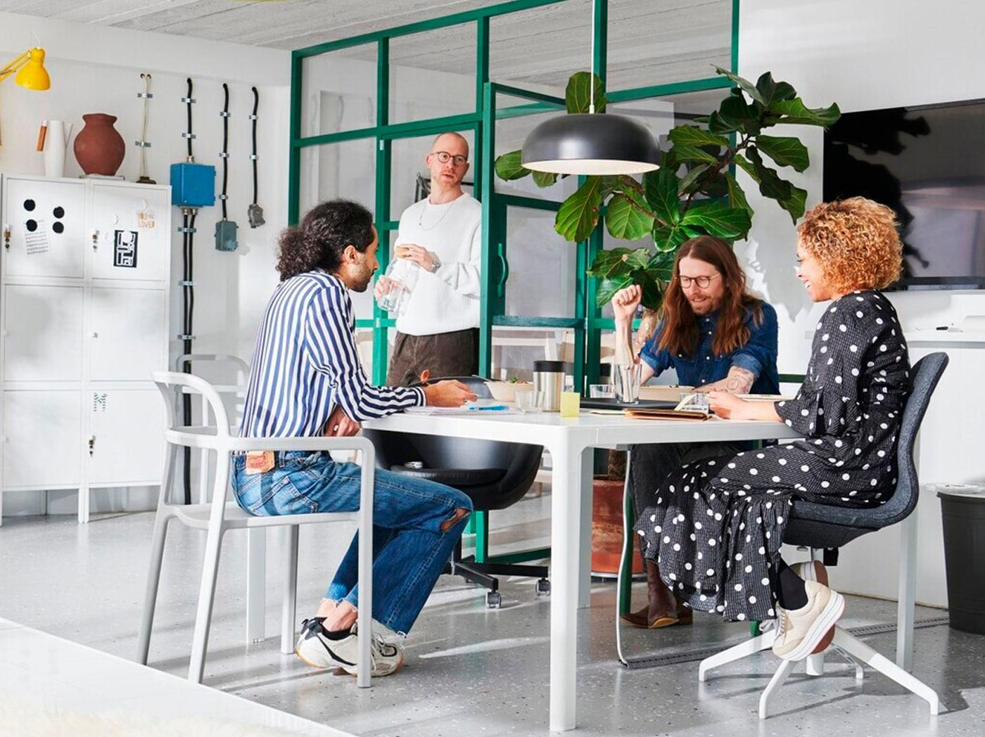 Traja ľudia, ktorí sedia za stolom a diskutujú