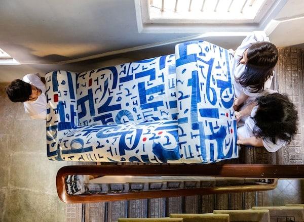 Traja ľudia s tmavými vlasmi nesú modro-bielu pohovku KLIPPAN do schodov.