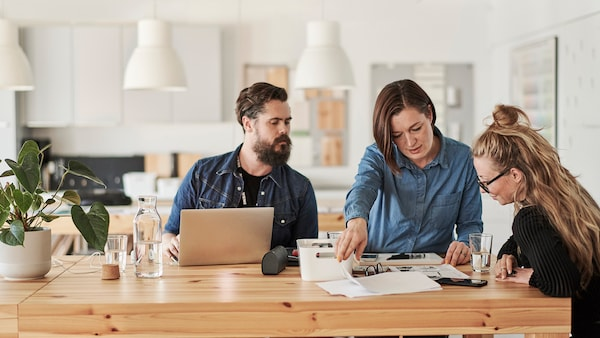 Traja ľudia sa rozprávajú pri stole a plánujú.