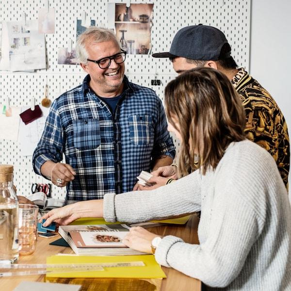Traja ľudia sedia pri stole a komunikujú na podujatí v IKEA.