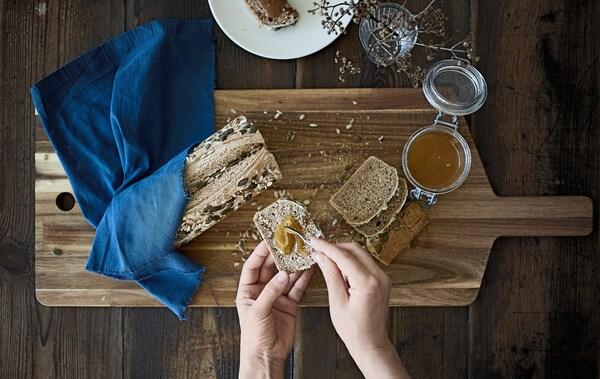 Tranche de pain aux graines et pot de miel, sur une planche en bois.
