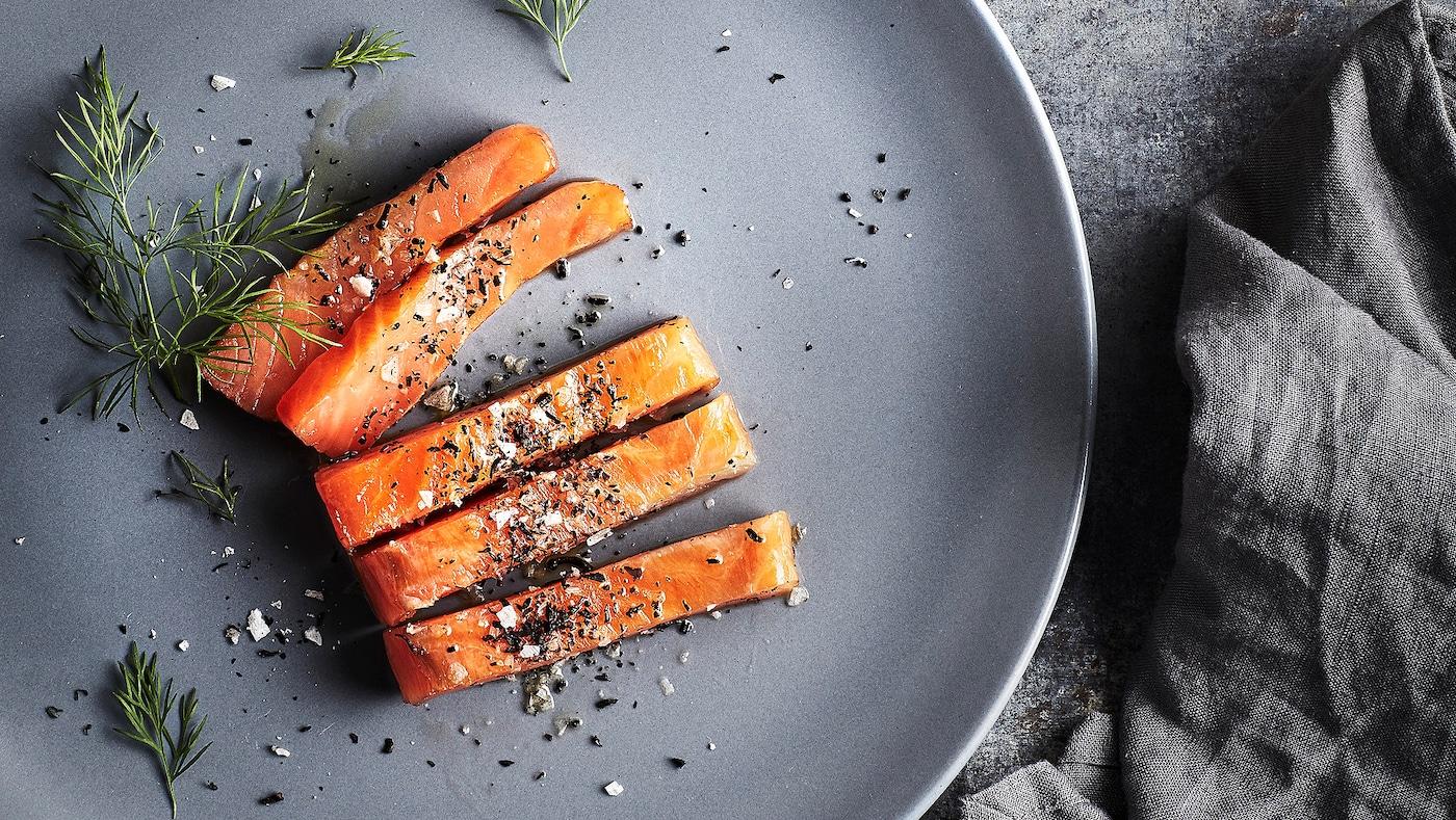 Tranches de saumon saupoudrées de sel, de poivre et d'aneth sur une assiette grise. À côté, une serviette grise.