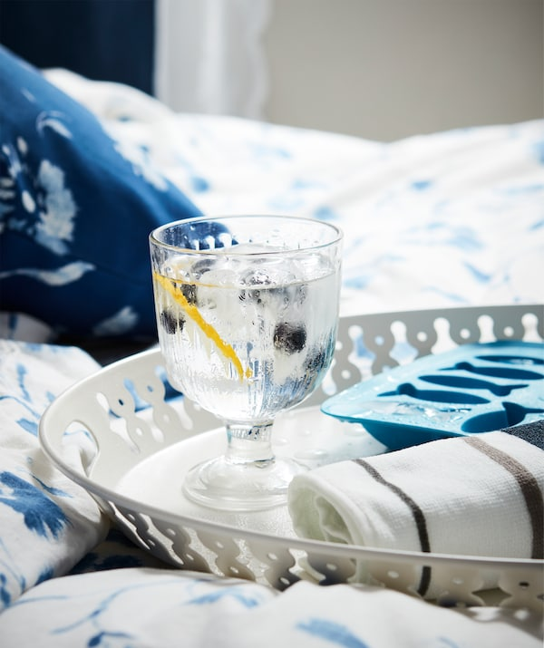 Tray holding a glass of water with ice and berries, a rolled-up towel and ice-cube tray, all resting on a softly made bed.