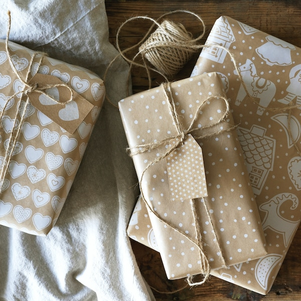 Tre gaver på et bord i beige og hvid.