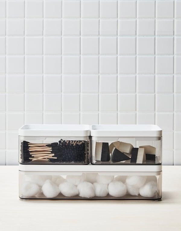 tre gennemsigtige kasser til opbevaring står på et badeværelse. I kasserne er der vatrodeller og make-up ting