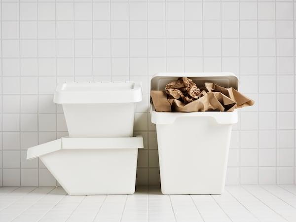 Tre hvite SORTERA bøtter med lokk, den ene full av brunt papir, i et hvitt flislagt rom.