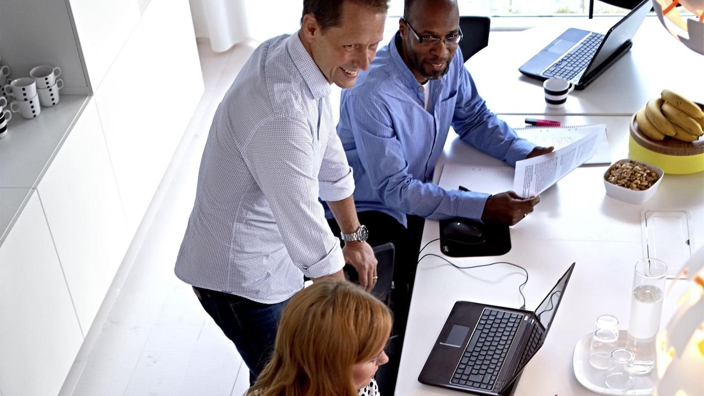 Tre mennesker jobber foran en PC.