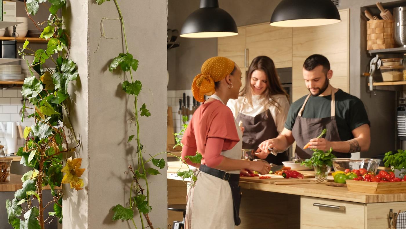 Tre personer med forklæder på står ved en stor køkkenø i et stort køkken og laver mad. Slyngplanter snor sig op ad en stolpe i nærheden.