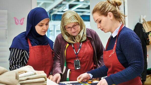 Tre rifugiate che offrono servizi di cucitura ai clienti in un negozio IKEA esaminano insieme un motivo per un tessuto.