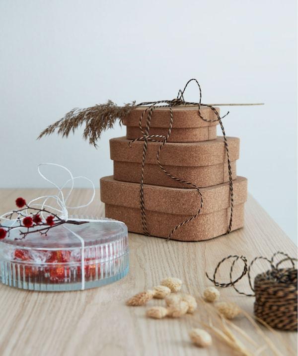 Tre scatole in sughero tenute insieme da un nastro e decorate con un rametto, accanto a un barattolo di vetro pieno di caramelle - IKEA