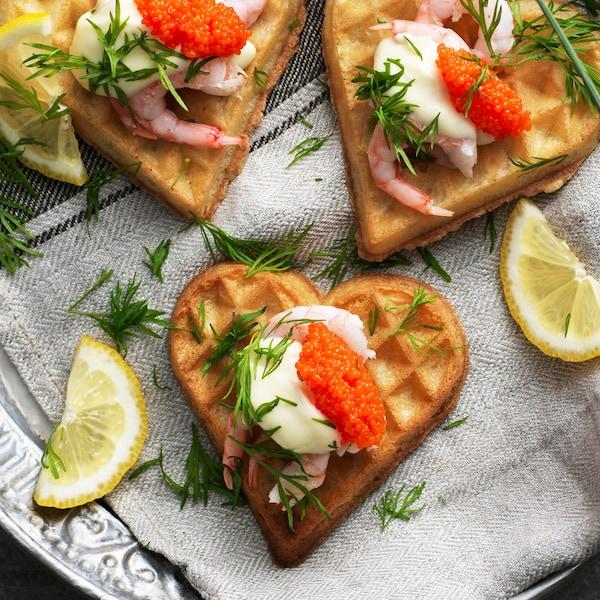 Tre VÅFFLOR vaffelhjerter med reker, majones, tangkorn og dill på en tallerken med et kjøkkenhåndkle.