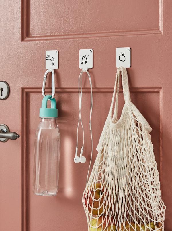 Tre vita PLUTT självhäftande krokar fästa på en dörr och dekorerade med tips på vad man ska hänga upp ritade med en svart penna.