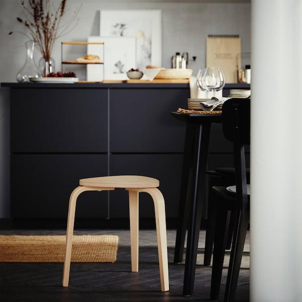 Trebent pall i björk, svart skåp med dekorativa föremål ovanpå samt ett bord och två stolar i svart.