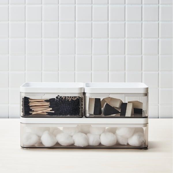 Trei cutii BROGRUND cu bile de vată și bețișoare de bumbac pe un blat alb sprijinit de un perete cu faianță albă.