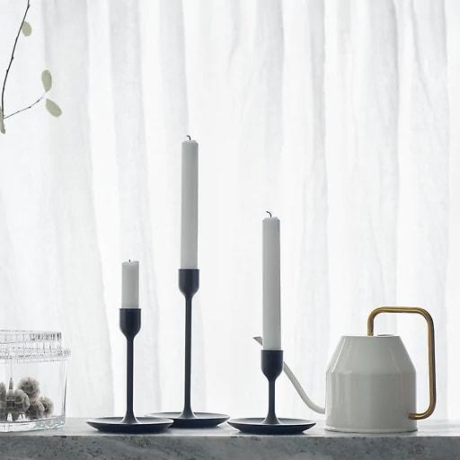Tres candelabros negros de distintas alturas sobre un fondo blanco con una regadera y tarros de vidrio.