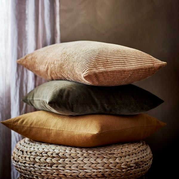 Tres cojines con fundas diferentes apilados unos encima de otros en un taburete ALSEDA junto a una ventana con cortinas.