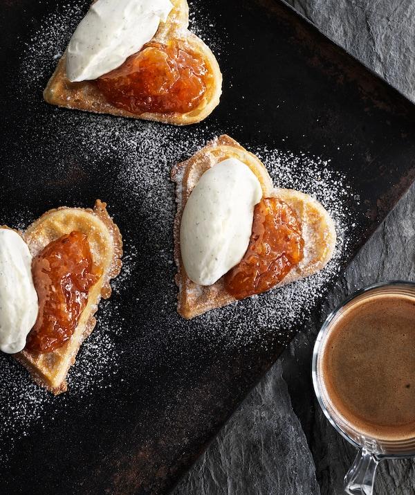 Tres gofres en forma de corazón con mermelada y crema batida en una placa de horno, café en una taza de vidrio a un lado.
