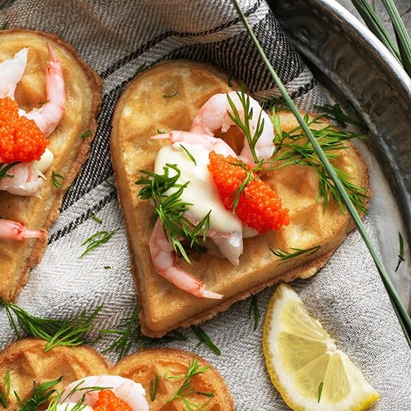 Tres gofres VÅFFLOR en forma de corazón con gambas, mayonesa, perlas de algas y eneldo en un plato con un paño de cocina.