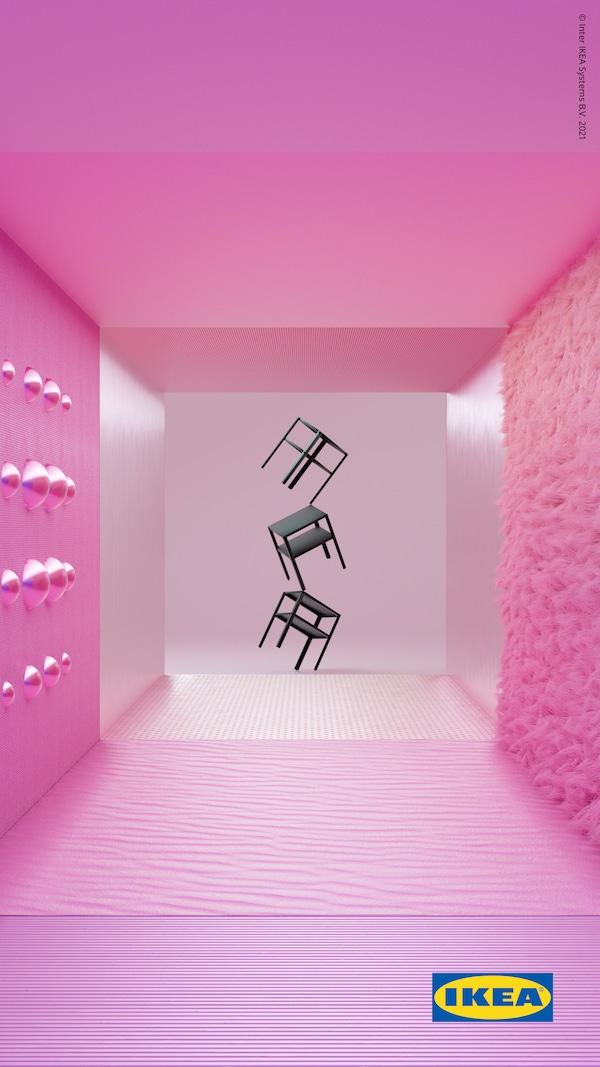 Tres mesas de noite KNARREVIK negras en equilibrio sobre unha pata unha enriba da outra fronte a unha parede rosa estriada.