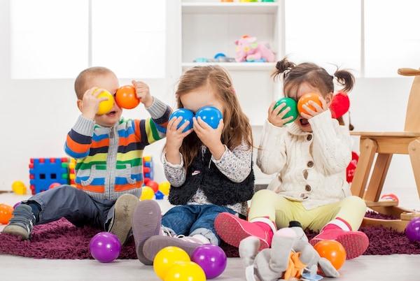 Tres niños, dos niñas y un niño jugando en un piso blanco con juguetes de colores. Se tapan los ojos con pelotas de colores de materiales responsables para que jueguen con seguridad en casa. Hay pelotas azules, moradas, amarillas, verdes y naranjas, con un par de juguetes de madera de fondo también.