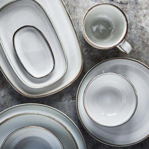 Três pilhas de tigelas, pratos e loiça para servir em cinzento claro com uma chávena ao lado, sobre uma superfície em cinzento.