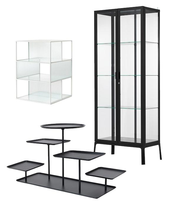 Tres productos diseñados para exponer colecciones. Armario alto con puertas de vidrio MILSBO con marco negro, caja vitrina SAMMANHANG y soporte de exposición SAMMANHANG con 5 bandejas.