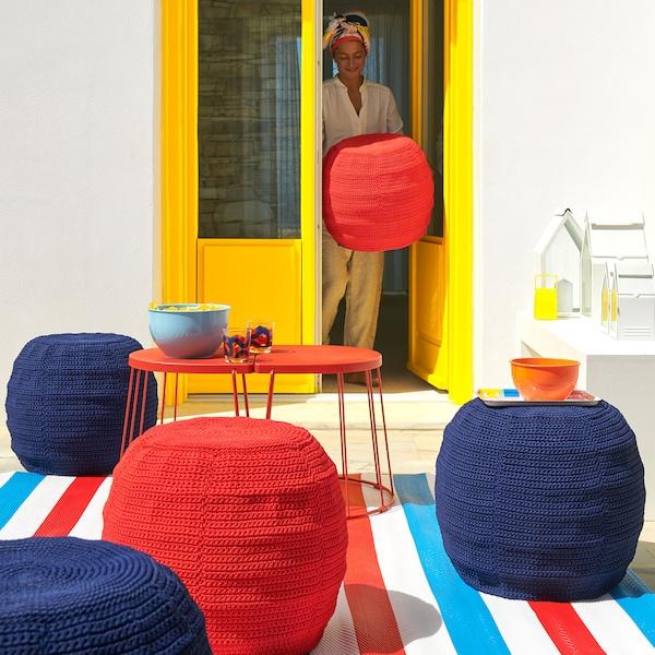 Tres pufs OTTERÖN/INNERSKÄR con fundas tejidas en rojo o azul en un soleado patio.