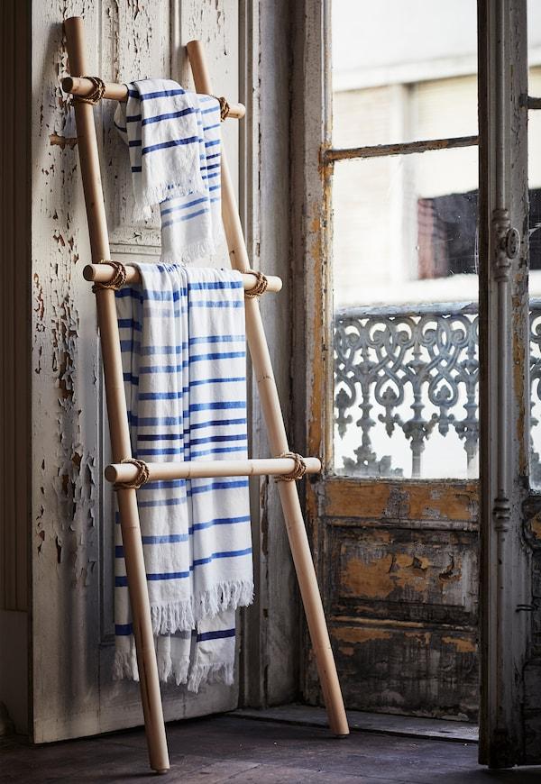 Tres toallas de spa IKEA TÄNKVÄRD con rayas blancas y azules colgadas en un soporte para ropa de ratán en un baño.