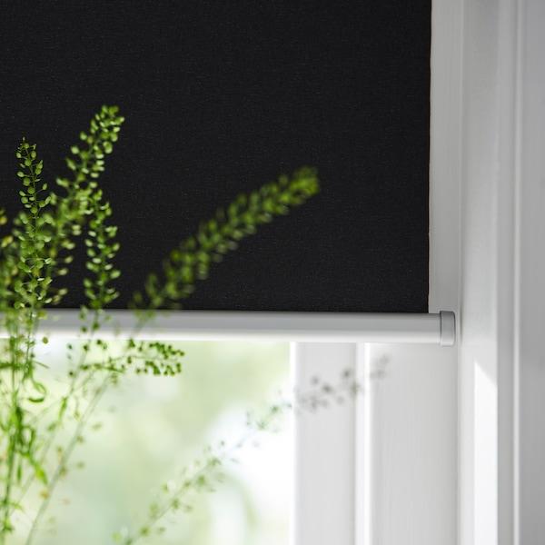 TRETUR gardin i ett fönster där en växt syns framför.