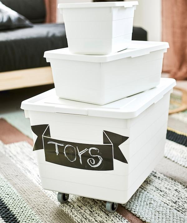 Три білі коробки для зберігання різного розміру, розміщені одна на одній на смугастому килимку. На нижній коробці з коліщатками розміщено наліпку «Іграшки».