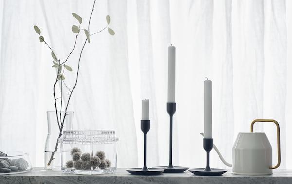 Tri crna svijećnjaka različitih visina na bijeloj pozadini s kantom za zalijevanje i staklenkama.