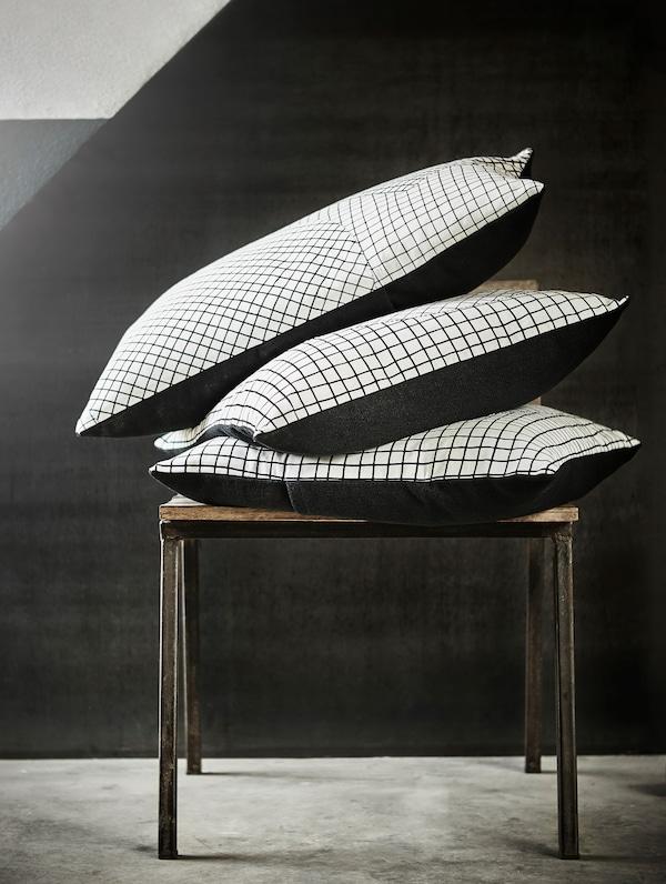 Три HANTVERK ХАНТВЕРК подушки, вироблені вручну в Йорданії, складені стопкою на невеликому столі.
