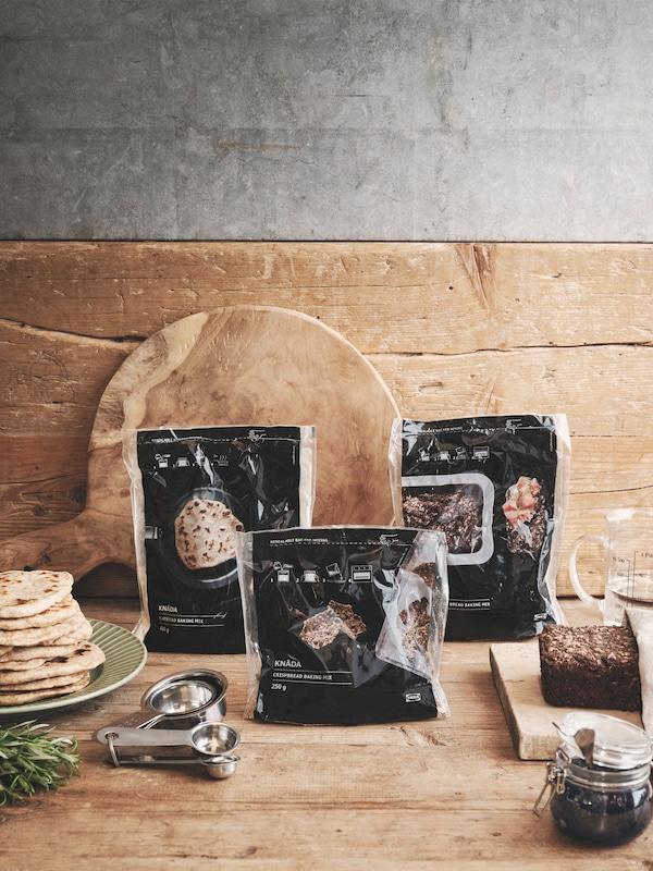 Tri KNÅDA smjese za pripremu kruha u pakiranjima na drvenoj kuhinjskoj površini.