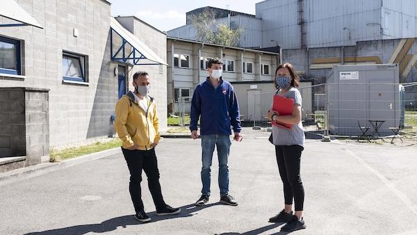Tři lidé stojí na dvorku průmyslového areálu.