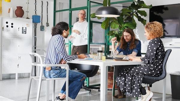 Tři lidi sedíci za bílým stolem uprostřed diskuze