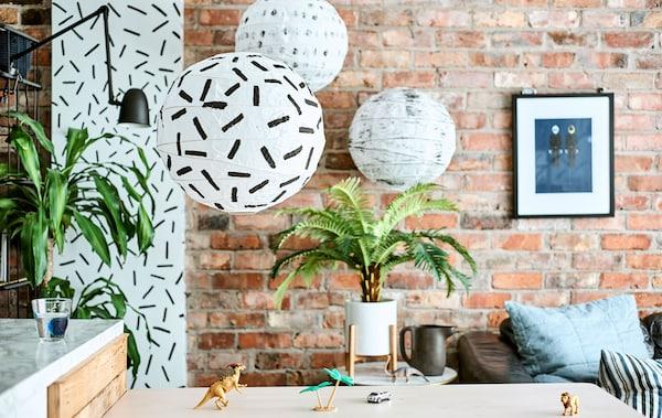 Tri okrúhle lampy s čierno-bielym vzorom zavesené nad stolom s hračkárskymi figúrkami v kuchyni s jedálňou s tehlovými stenami.