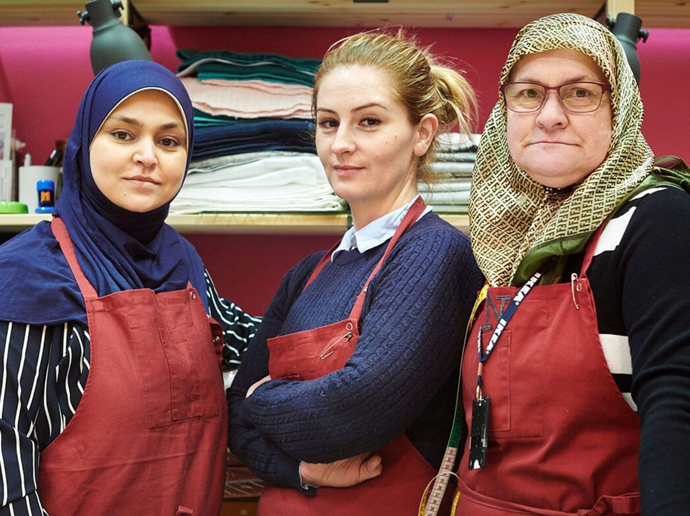 Tri sebavedomé ženy pózujú v obchode s látkami v obchodnom dome IKEA, aby si uctili Svetový deň utečencov 20. júna.