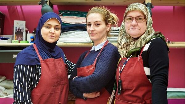 Tři sebevědomé ženy vystupující v textilním oddělení obchodu IKEA na počest Světového dne uprchlíků 20. června.