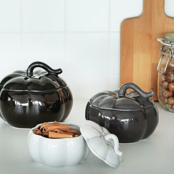 Trois bols en forme de citrouille posés sur une table de cuisine, dont un est ouvert et rempli de bâtons de cannelle.