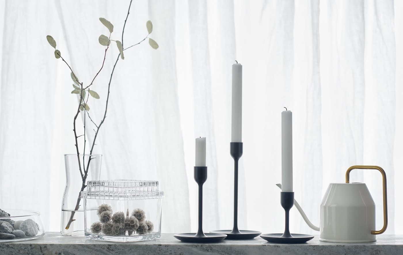 Trois chandeliers noirs de hauteurs variées placés devant un rideau blanc et à proximité d'un arrosoir et d'un contenant en verre.