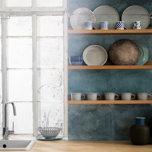 Trois cimaises MÅLERÅS utilisées dans une cuisine pour exposer des tasses et des assiettes contre un mur texturé bleu-vert.