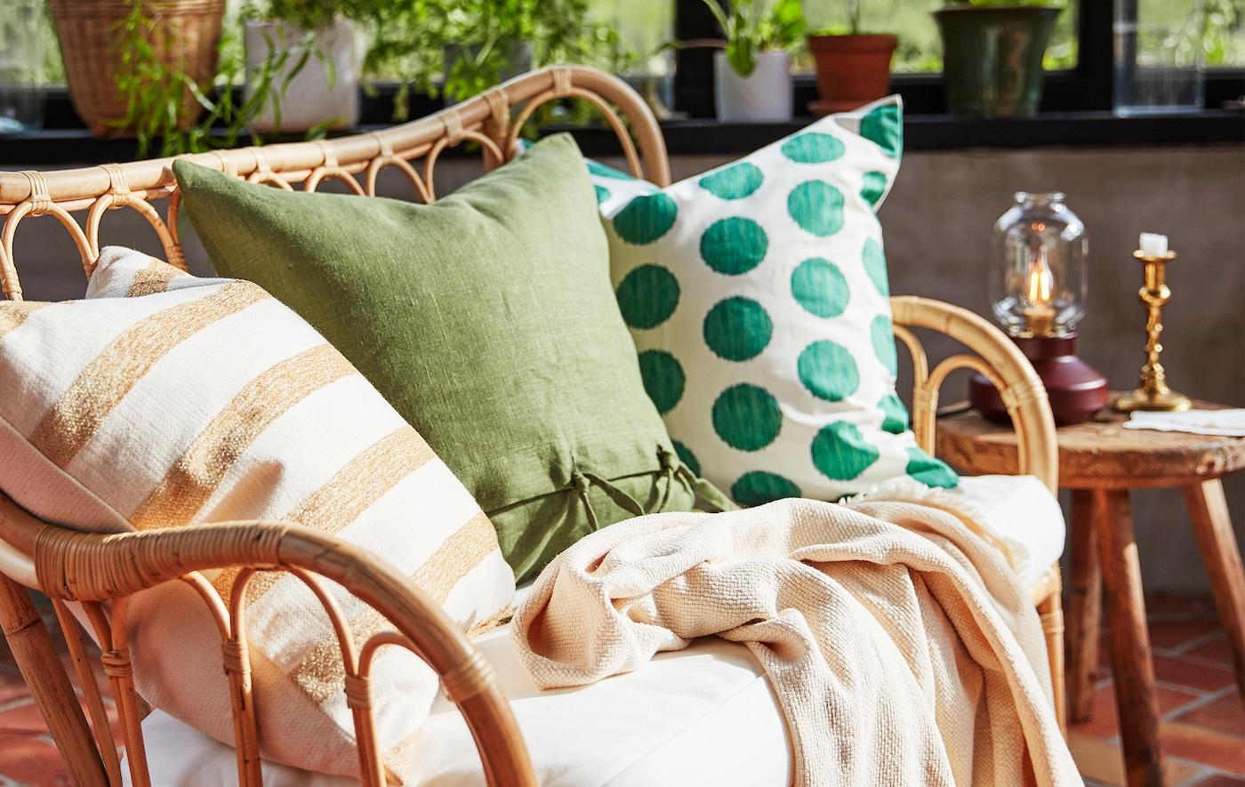 Trois coussins avec des motifs différents dans des teintes douces, placés sur un canapé en rotin naturel dans une salle de séjour.