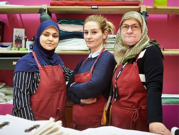 Trois femmes posant fièrement au département textile d'un magasin IKEA à l'occasion de la Journée mondiale des Réfugiés du 20 juin.