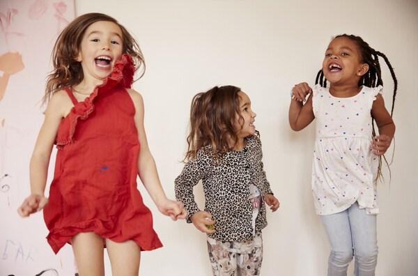 Trois fillettes qui dansent, sourient et sautent.